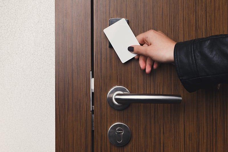Hand houdt een sleutelkaart of badge vast tegen een elektronisch slot voor toegangscontrole.